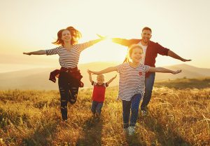 Family running in nature with sunset | Integrity Financial